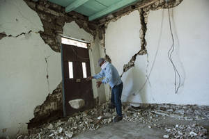 Photo - Mynor Fuentes checks his home after it was damaged during an earthquake in San Pedro, Guatemala, Monday, July 7, 2014. A magnitude-6.9 earthquake on the Pacific Coast jolted a wide area of southern Mexico and Central America Monday. (AP Photo/Oliver de Ros)