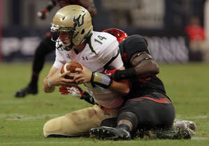 Photo - South Florida quarterback Mike White, left, is tackled by Houston linebacker Derrick Mathews during the second quarter of an NCAA college football game Thursday, Oct. 31, 2013, in Houston. (AP Photo/Houston Chronicle, James Nielsen) MANDATORY CREDIT