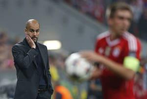 Photo - Bayern head coach Pep Guardiola, left, looks to team captain Philipp Lahm during the Champions League semifinal second leg soccer match between Bayern Munich and Real Madrid at the Allianz Arena in Munich, southern Germany, Tuesday, April 29, 2014. (AP Photo/Matthias Schrader)