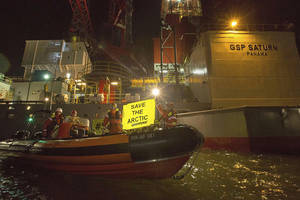 Photo - This image made available by environmental organization Greenpeace shows activists boarding a rig contracted by Russia's Gazprom in the port of IJmuiden, Netherlands, on Tuesday, May 27, 2014. Greenpeace said 30 activists in the Dutch port of IJmuiden on Tuesday boarded a rig contracted by Russia's Gazprom to drill in the Pechora Sea. Greenpeace said they were removed after five hours. (AP Photo/Bas Beentjes, Greenpeace)  NO ARCHIVE