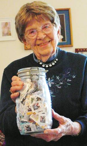 Photo - Polly Nikolaisen, 91, shows a jar of stamps June 25 in Kalispell, Mont. Nikolaisen has found a way to help tuberculosis patients and handicapped children by working from her easy chair, collecting canceled stamps for an international charity organization.  AP Photo
