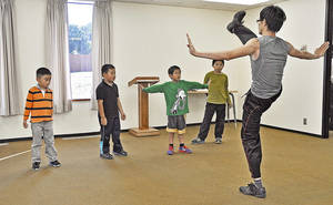 Photo - Kung Fu instructor Carl Ke, shows his class a basic move during Chinese culture classes at Trinity International Baptist Church Sunday, October 6, 2013. Photo by M. Tim Blake, for The Oklahoman