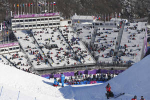 Photo - Spectators watch the women's snowboard slopestyle qualifying at the Rosa Khutor Extreme Park ahead of the 2014 Winter Olympics, Thursday, Feb. 6, 2014, in Krasnaya Polyana, Russia. (AP Photo/Sergei Grits)