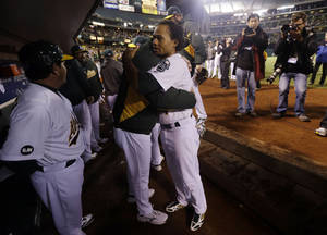 Photo -   Oakland Athletics manager Bob Melvin hugs Coco Crisp, right, after the A's lost 6-0 to the Detroit Tigers in Game 5 of an American League division baseball series in Oakland, Calif., Thursday, Oct. 11, 2012. (AP Photo/Marcio Jose Sanchez)