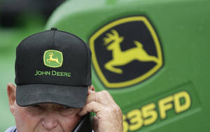 Photo - FILE - In this Sept. 11, 2014 file photo, a John Deere tractor is on display behind a man wearing a John Deere cap at the annual Husker Harvest Days agriculture fair in Grand Island, Neb. Deere & Company reports quarterly earnings on Wednesday, May 14, 2014.  (AP Photo/Nati Harnik, File)