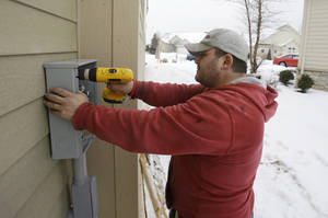 Photo - In this Friday, Jan. 10, 2014, photo, Paquale Cocca installs a new electrical box on a new home, in Pepper Pike, Ohio. The Commerce Department releases housing starts for January on Wednesday, Feb. 19, 2014. (AP Photo/Tony Dejak)