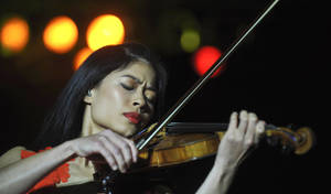Photo - FIL:E - This is a Monday, Oct. 18, 2010 file photo of Internationally renown  violinist Vanessa Mae as she performs during her concert in Prague, Czech Republic. The manager of musician Vanessa Mae says the musician will be swapping her violin for skis to compete at the Winter Olympics. Giles Howard says the classical-pop violinist has qualified for the Thai team at the Sochi games. The International Ski Federation published rankings on Monday Jan. 20, 2014 confirming Mae has met the qualifying criteria to compete at Sochi. (AP Photo/CTK, Rene Volfik) ** SLOVAKIA OUT **