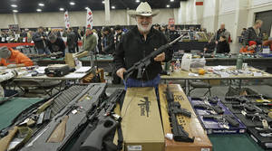 "Photo - FILE - In this Jan. 6, 2013 file photo, Ken Haiterman, of Pioneer Market, holds a CMMG 5.56mm AR 15 during the 2013 Rocky Mountain Gun Show in Sandy, Utah. A bipartisan quartet of senators, including two National Rifle Association members and two with ""F"" ratings from the potent firearms lobby, are quietly trying to reach compromise on expanding the requirement for gun-sale background checks. (AP Photo/Rick Bowmer, File)"