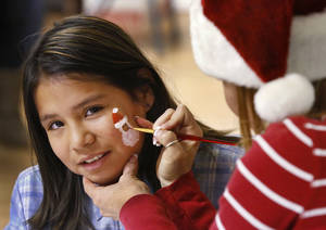 photo - Desirea, 9, has a Santa face painted on her by Kelly Long, a volunteer from TLC Custom Homes.