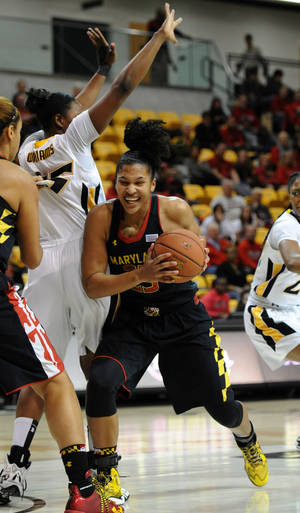 Photo - Maryland's Alyssa Thomas, right, drives to the basket as Towson's Nyree Williams defends in the first half of an NCAA college basketball game on Saturday, Nov. 23, 2013, in Towson, Md. (AP Photo/Gail Burton)