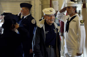 "Photo -   Staff Sergeant David Thatcher, center, is saluted as he enters the USS Hornet before a news conference to commemorate the 70th Anniversary of the Tokyo attack by the Doolittle Raiders in Alameda, Calif., Saturday, May 5, 2012. Survivors of a daring World War II aerial bombing of Japan are gathering in Alameda on the 70th anniversary of the attack. The ""Doolittle Raiders"" have been credited with lifting the nation's spirits after Pearl Harbor. (AP Photo/Jeff Chiu)"