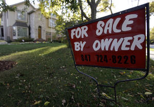 photo - FILE - This Wednesday, Oct. 10, 2012  file photo shows a for-sale sign at a home in Glenview, Ill.An index measuring the number of Americans who signed contracts to buy homes in October jumped to nearly its highest level in almost six years. Steady job gains and record-low mortgage rates have made home buying more attractive. (AP Photo/Nam Y. Huh, File)