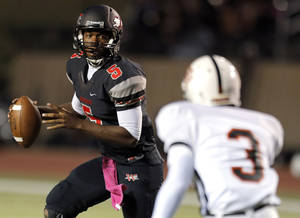photo - Westmoore&#039;s Jhames West looks to make a pass as Putnam City&#039;s J.D. Clark defends during the high school football game between Moore and Putnam City at Westmoore High School,  Thursday, Oct. 4, 2012. Photo by Sarah Phipps, The Oklahoman
