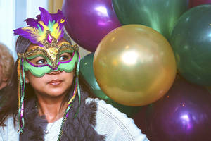 Photo - Above: Maricha Thompson dons her Mardi Gras mask while serving refreshments from Midway Grocery at a Zydeco Jambalaya Cookoff Saturday at the Santa Fe Depot. PHOTOS BY  LYNETTE LOBBAN,  FOR THE OKLAHOMAN