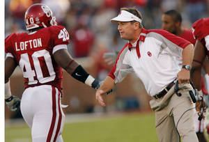 Photo - Oklahoma coach Bob Stoops slaps hands with Curtis Lofton (40) after the Sooners made a defensive stop against Missouri during the first half of the college football game between  the University of Oklahoma Sooners (OU) and the University of Missouri Tigers (MU) at the Gaylord Family Oklahoma Memorial Stadium on Saturday, Oct. 13, 2007, in Norman, Okla.