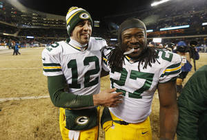 Photo - Green Bay Packers quarterback Aaron Rodgers (12) celebrates with running back Eddie Lacy (27) after their NFL football game against the Chicago Bears, Sunday, Dec. 29, 2013, in Chicago. The Packers won 33-28 to capture the NFC North title. (AP Photo/Charles Rex Arbogast)