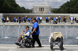 Photo -   FILE - In this Wednesday, June 6, 2012 file photo, retired Army Infantry Pfc. Marvin Kincaid, 85, of Thayer, Mo., left, is accompanied by Dennis Hobbs at the the World War II Memorial in Washington as honor flight WWII veterans and helpers wearing blue or white t-shirts, visited the site on the 68th anniversary of D-Day. The Lincoln Memorial is in the background. As many as 100 World War II veterans missed their chance to travel to Washington to see their war's memorial after about $110,000 disappeared from a Kansas nonprofit that organized free trips for them. Central Prairie Honor Flights program director, LaVeta Miller, was charged in October 2012 with two counts of theft by deception. (AP Photo/Jacquelyn Martin)