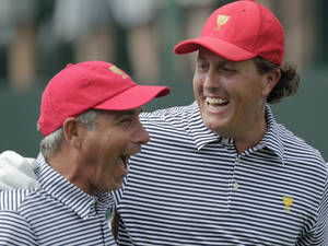Photo - United States' Phil Mickelson, right, and team captain Fred Couples laugh together while walking down the first tee during a foursome match against the International team at the Presidents Cup golf tournament at Muirfield Village Golf Club Friday, Oct. 4, 2013, in Dublin, Ohio. (AP Photo/Jay LaPrete)