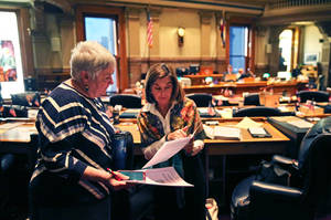 Photo - In this Jan. 22, 2014 photo, Colorado Democratic state senators Mary Hodge, left, and Gail Schwartz talk inside the chambers of the Colorado State Senate, at the Capitol, in Denver. Sen. Hodge has proposed a bill requiring better informing landowners and buyers about their property rights, which often doesn't include mineral rights below the surface. (AP Photo/Brennan Linsley)