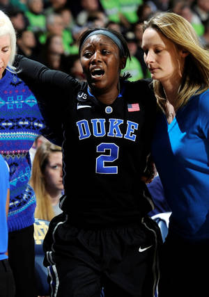 Photo - Duke guard Alexis Jones is helped to the locker room after being injured in the second half of an NCAA college basketball game with Duke Sunday, Feb. 23, 2014 in South Bend, Ind. Notre Dame won 81-70 with Jones scoring 15 points.  (AP Photo/Joe Raymond)