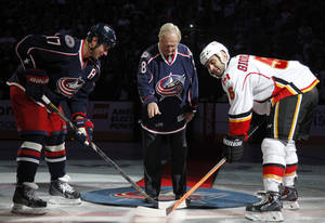 Photo - Jack Nicklaus, center, drops the puck between Columbus Blue Jackets' Brandon Dubinsky, left, and Calgary Flames' Mark Giordano during the opening ceremony before an NHL hockey game in Columbus, Ohio, Friday, Oct. 4, 2013. (AP Photo/Paul Vernon)