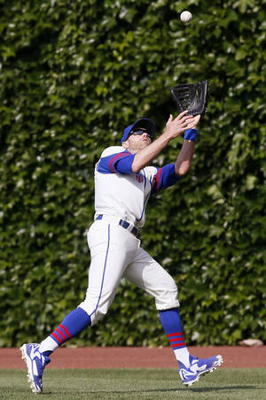 Photo - Chicago Cubs right fielder Nate Schierholtz catches a fly ball hit by the Miami Marlins' Jeff Mathis during the ninth inning of a baseball game on Sunday, June 8, 2014, in Chicago. (AP Photo/Andrew A. Nelles)