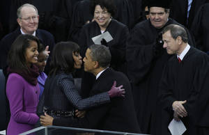 Photo - President Barack Obama kisses his wife Michelle after the ceremonial swearing-in at the U.S. Capitol during the 57th Presidential Inauguration in Washington, Monday, Jan. 21, 2013. Right is Chief Justice John Roberts. (AP Photo/Paul Sancya)