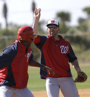 photo - Washington Nationals infielder Danny Espinosa, right, tosses the ball as he chases Roger Bernadina (33) as part of a rundown drill during a spring training baseball workout Tuesday, Feb. 19, 2013, in Viera, Fla. (AP Photo/David J. Phillip)