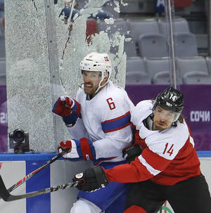 Photo - Glass encasing the penalty box shatters as Austria forward Andreas Nodl checks Norway defenseman Jonas Holos in the second period of a men's ice hockey game at the 2014 Winter Olympics, Sunday, Feb. 16, 2014, in Sochi, Russia. (AP Photo/Mark Humphrey)