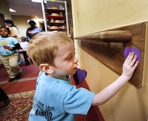 Photo - Pre-kindergarten student Jude McDermitt, from West Nichols Hills, places a paper heart on the wall of Canterbury's Assisted Living Center for Valentine's Day. PHOTO BY DAVID MCDANIEL, THE OKLAHOMAN <strong>David McDaniel - The Oklahoman</strong>