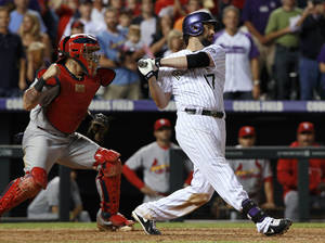 Photo - St. Louis Cardinals catcher Yadier Molina, left, starts to celebrate after Colorado Rockies' Todd Helton struck out with the bases loaded for the final out in the Cardinals' 4-3 victory in a baseball game in Denver on Wednesday, Sept. 18, 2013. (AP Photo/David Zalubowski)