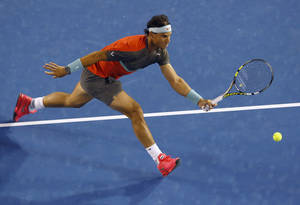 Photo - Rafael Nadal of Spain reaches for a shot to Gael Monfils of France during their third round match at the Australian Open tennis championship in Melbourne, Australia, Saturday, Jan. 18, 2014.(AP Photo/Eugene Hoshiko)