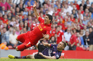 Photo -   Liverpool's Luis Suarez tussles with Arsenal's Thomas Vermaelen, right, during their English Premier League match at Anfield, Liverpool England Sunday Sept. 2, 2012. Arsenal won the match 2-0. (AP Photo/ Peter Byrne/PA) UNITED KINGDOM OUT - NO SALES - NO ARCHIVES