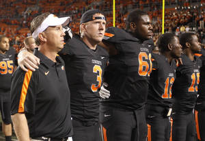Photo - Oklahoma State quarterback Brandon Weeden, second from left, joins in with offensive coordinator Todd Monken, left, and teammate Michael Bowie, (61), as the team sings the alma mater with their fans following an NCAA college football game against Arizona in Stillwater, Okla., Thursday, Sept. 8, 2011. Oklahoma State won 37-14.  (AP Photo/Sue Ogrocki) ORG XMIT: OKSO113