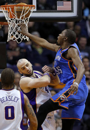 Photo - Oklahoma City Thunder center Kevin Durant, right, scores over Phoenix Suns center Marcin Gortat during the second half of an NBA basketball game, Monday, Jan. 14, 2013, in Phoenix. The Thunder won 102-90. (AP Photo/Matt York)