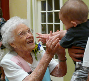 Photo - Thelma Barnes reaches for Colin Townsend, 11 months, at her 104th birthday party Saturday at Rivermont Retirement Community in Norman. Barnes lives independently at the center and walks nearly a mile most days. PHOTO BY CONNIE HEFNER, FOR THE OKLAHOMAN