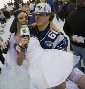 "Photo - File-This Jan. 29, 2008 file photo shows Ines Gomez Mont, a reporter from TV Azteca in Mexico, wearing a wedding dress as she is carried by New England Patriots center Lonie Paxton while interviewing him during media day for the Super Bowl XLII football game in Glendale, Ariz.  Once a serious endeavor, media day is now a forum for credentialed ""media"" such as Mont. The entertainment reporter for Mexico's TV Azteca showed up in Glendale, Ariz., wearing a scanty white wedding dress and towering red pumps. She spent the next two hours trying to persuade someone, anyone, to accept her marriage proposal. (AP Photo/The Arizona Republic, Michael Chow, File)"