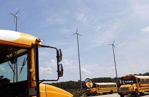 Photo - ADVANCE FOR SATURDAY, JULY 12 - Wind turbines turn in the breeze on Wednesday, July 2, 2014, at a Virginia Beach Public School bus yard in Virginia Beach, Va. Budgets are tight, so school divisions around the nation are looking for ways to cut costs. In 2005, the U.S. Energy Department launched the Wind for Schools project to help those interested in tapping into that power source. By last year, more than 130 systems had been installed at schools in 11 states, including more than a dozen across Virginia and North Carolina. (AP Photo/The Virginian-Pilot, Vicki Cronis-Nohe)