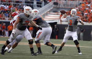 photo - Oklahoma State's Brandon Weeden looks to throw during Saturday's game in Stillwater. Photo by Sarah Phipps, The Oklahoman