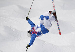 Photo - France's Guilbaut Colas jumps during freestyle skiing moguls training at the Rosa Khutor Extreme Park  ahead of the 2014 Winter Olympics, Friday, Feb. 7, 2014, in Krasnaya Polyana, Russia. (AP Photo/Andy Wong)