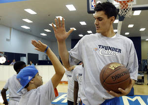 Photo - OKLAHOMA CITY THUNDER NBA BASKETBALL: Steven Adams high-fives a youth during the Thunder Youth Basketball mini-camp following a press conference at the Thunder Events center, Saturday, July 29, 2013. Photo by Sarah Phipps, The Oklahoman