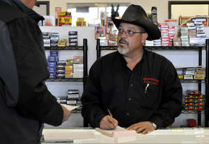 Photo -   In this Saturday, Nov. 10, 2012 photo, store owner Mark Chavez, right, signs up a Belen rancher for the Gunhawk Firearms coyote hunt in Los Lunas, N.M. Chavez, who has faced two weeks of angry phone calls and protests - and even a threat to his life - is not backing down from holding the contest, in which New Mexico hunters have two days this weekend to shoot and kill as many coyotes as they can. The winners get their choice of a free shotgun or a pair of semi-automatic rifles. (AP Photo/Albuquerque Journal, Marla Brose)