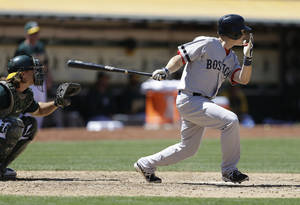 Photo - Boston Red Sox's Brock Holt swings for an RBI single off Oakland Athletics' Bartolo Colon in the seventh inning of a baseball game Sunday, July 14, 2013, in Oakland, Calif. (AP Photo/Ben Margot)