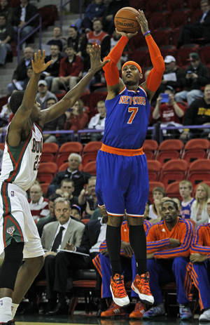 Photo - New York Knicks forward Carmelo Anthony (7) shoots over Milwaukee Bucks forward Khris Middleton during the first half of an NBA preseason basketball game Wednesday, Oct. 23, 2013, in Green Bay, Wis. (AP Photo/Matt Ludtke)