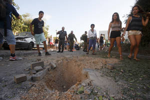 Photo - Israelis look at the crater caused by the impact of a rocket fired from Lebanon in kibbutz Gehser HaZiv outside Nahariya in northern Israel, Thursday, Aug. 22, 2013. Military spokesman Lt. Col. Peter Lerner said Thursday that three rockets landed in northern Israel, while one was shot down. (AP Photo/Jinipix)   ISRAEL OUT