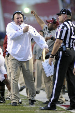 Photo - Arkansas coach Bret Bielema, left, talks to an official during the second quarter of an NCAA college football game against Texas A&M in Fayetteville, Ark., Saturday, Sept. 28, 2013. (AP Photo/Beth Hall)