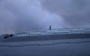 Photo - A worker walks along the roof of the Bolshoy Ice Dome at dusk while last minute preparations are underway, a day before the opening ceremony of the 2014 Winter Olympics, Thursday, Feb. 6, 2014, in Sochi, Russia. (AP Photo/Wong Maye-E)