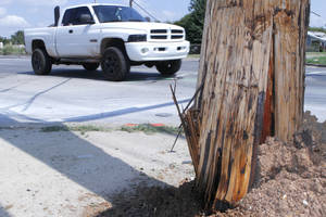 Photo - A truck passes the utility pole hit by a homicide victim's vehicle at SW 15 and S Pennsylvania Avenue. Police responded at 4:55 a.m. Saturday, Sept. 15, 2012, to an accident there and found Javier Collazo, 34, who had been shot, inside a sport utility vehicle that had hit a pole. <strong>David McDaniel - The Oklahoman</strong>