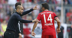 Photo - Bayern head coach Pep Guardiola of Spain, left, talks to Bayern's Claudio Pizarro of Peru during the German first division Bundesliga soccer match between FC Bayern Munich and SV Werder Bremen in Munich, southern Germany, Saturday, April 26, 2014. (AP Photo/Matthias Schrader)