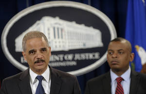 Photo - Attorney General Eric Holder, left, accompanied by Transportation Secretary Anthony Foxx, announces a $1.2 billion settlement with Toyota over its disclosure of safety problems, Wednesday, March 19, 2014, during a news conference at the Justice Department in Washington. (AP Photo/Susan Walsh)